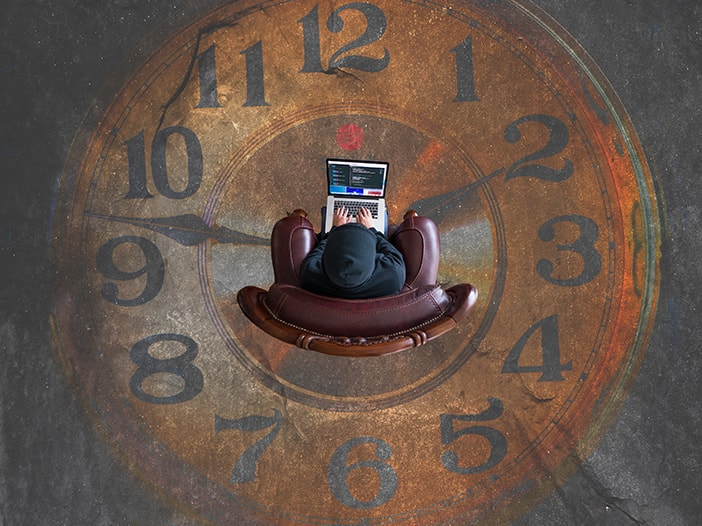 Image of individual coding on a laptop in a chair surrounded by a clockface.